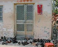 Patients' shoes piled outside the door to Dr. Fuda's clinic. - Copyright – Stock Photo / Register Mark
