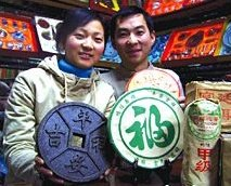 Yunnan couple displaying bricked pu cha (shu style) in tea shop. - Copyright – Stock Photo / Register Mark