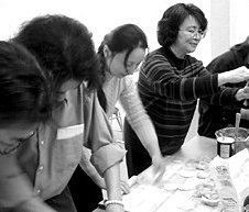 Aileen Huang leads attendees in a dumpling-making demonstration. - Copyright – Stock Photo / Register Mark